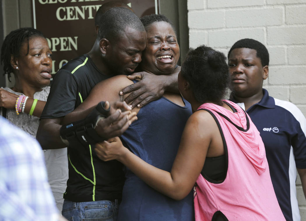 The mother, center, of two young children is comforted after she found them stabbed to death in their father's apartment in Houston. Court records show Jean Pierre Ndossoka, accused of killing hi ...