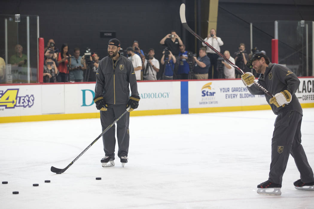 Vegas Golden Knights defenseman Deryk Engelland, left, looks on as NASCAR driver Kurt Busch takes a slap shot during a media event on Monday, Aug. 13, 2018, at City National Arena to promote the S ...