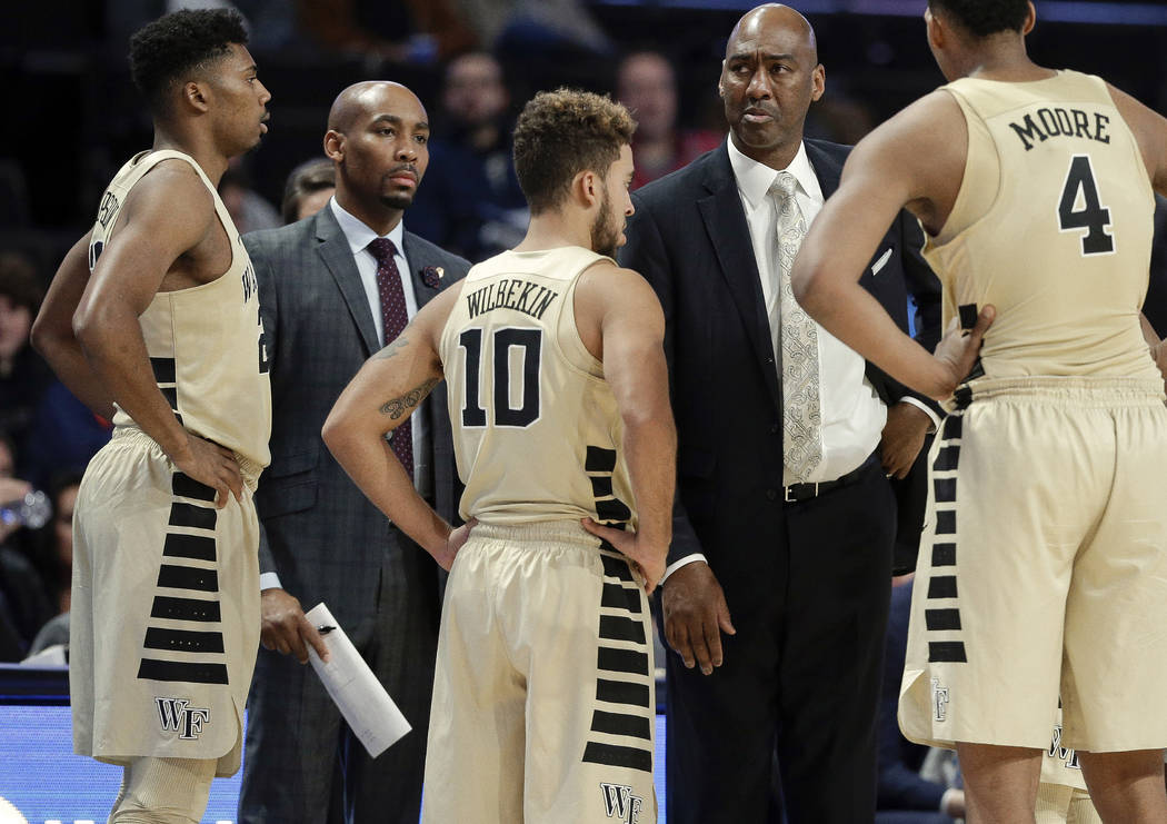 This photo from Nov. 28, 2017, shows Wake Forest assistant coach Jamill Jones, second from left, with the team and head coach Danny Manning, second from right, during the second half of an NCAA co ...