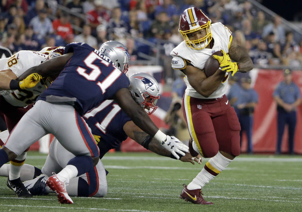 Washington Redskins running back Derrius Guice, right, evades New England Patriots linebacker Ja'Whaun Bentley (51) and defensive tackle Danny Shelton, center, during the first half of a preseason ...
