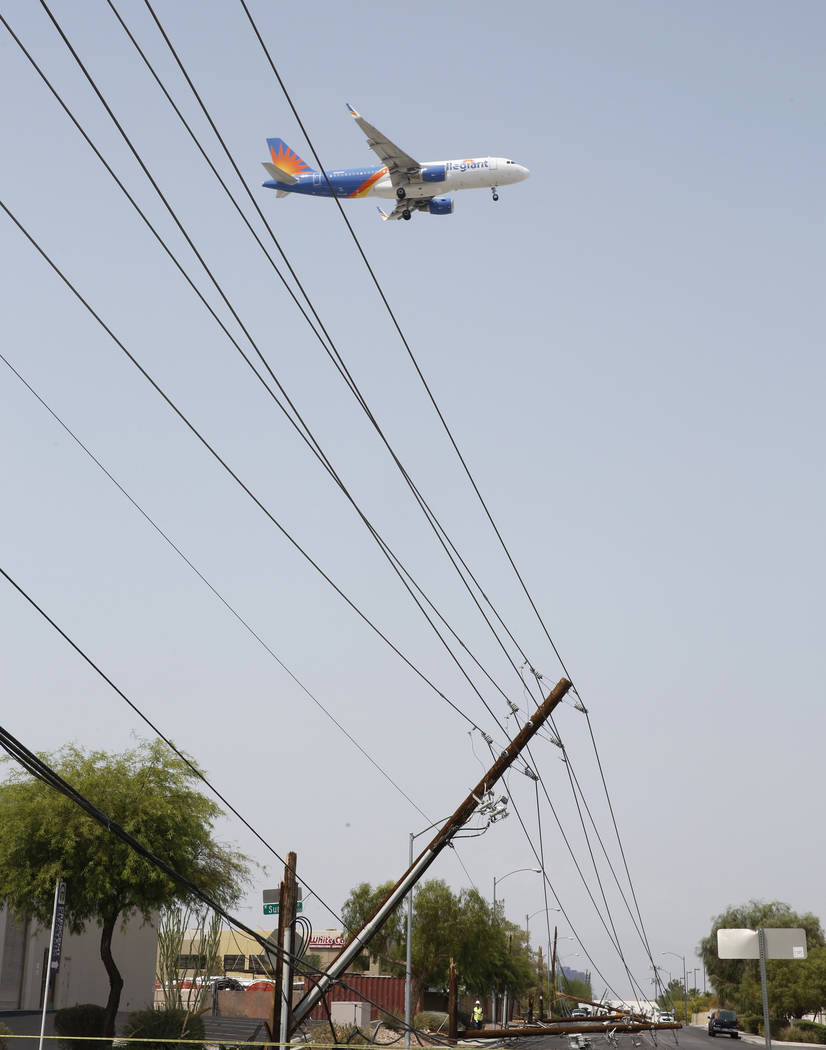 An Allegiant Airline plane flies over downed power lines at Sunset Rd., and Polaris Ave., caused by forklift on Friday, Aug. 10, 2018, in Las Vegas. Bizuayehu Tesfaye/Las Vegas Review-Journal @biz ...