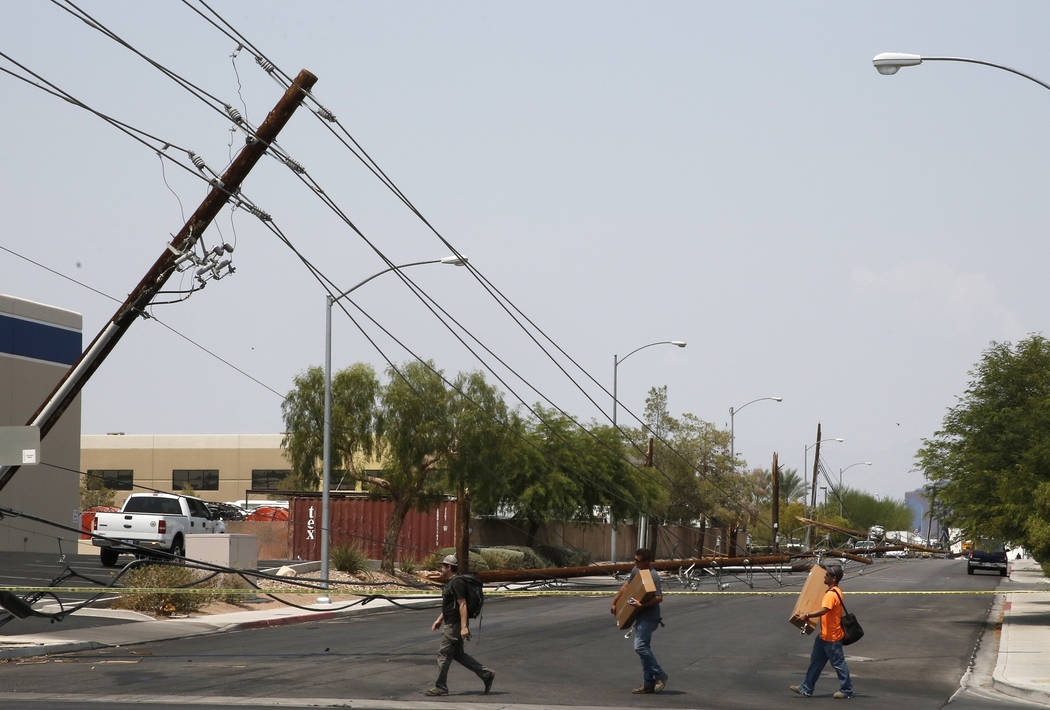 Pedestrians walk past downed power lines at Sunset Rd., and Polaris Ave., on Friday, Aug. 10, 2018, in Las Vegas. Forklift knocks down 13 power poles. Bizuayehu Tesfaye/Las Vegas Review-Journal @b ...