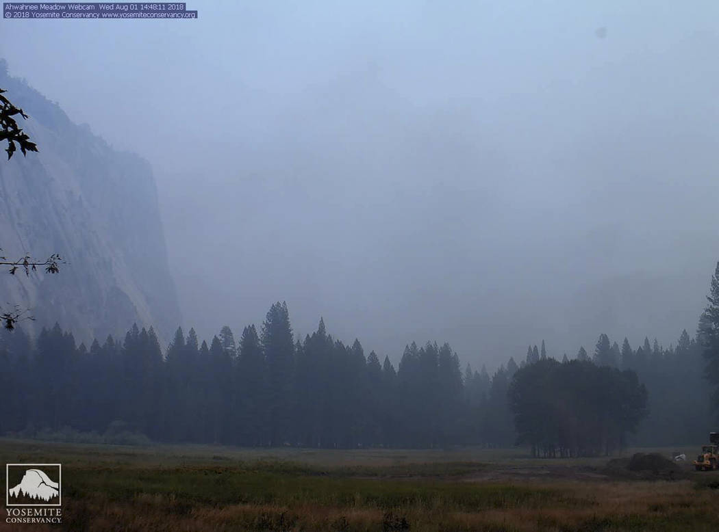 In an mage from a Yosemite Conservancy webcam, smoke from wildfires obscures the Ahwahnee Meadow at Yosemite National Park, Calif., Wednesday, Aug. 1, 2018. Yosemite National Park could reopen its ...