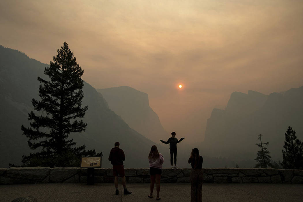 Hannah Whyatt poses for a friend's photo as smoke from the Ferguson fire fills Yosemite Valley in Yosemite National Park, Calif., in July 2018. (AP Photo/Noah Berger, File)