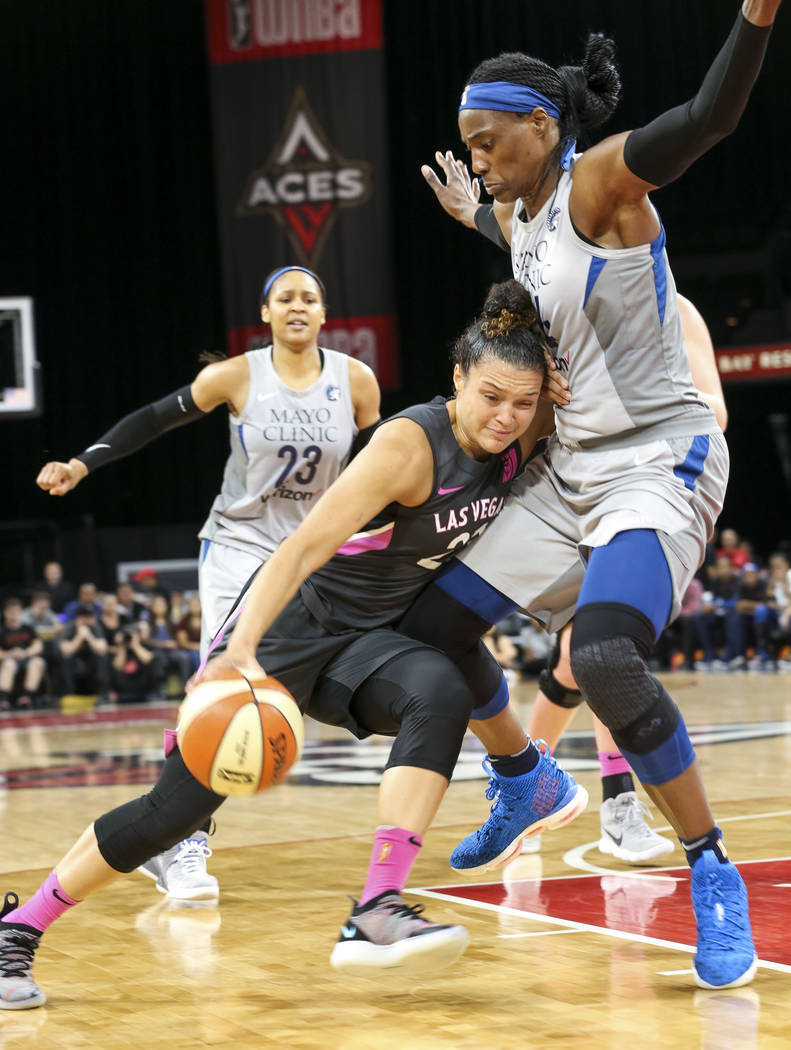 Las Vegas Aces guard Kayla McBride (21) drives the ball against Minnesota Lynx center Sylvia Fowles (34) during the first half of a WNBA basketball game at the Mandalay Bay Events Center in Las Ve ...