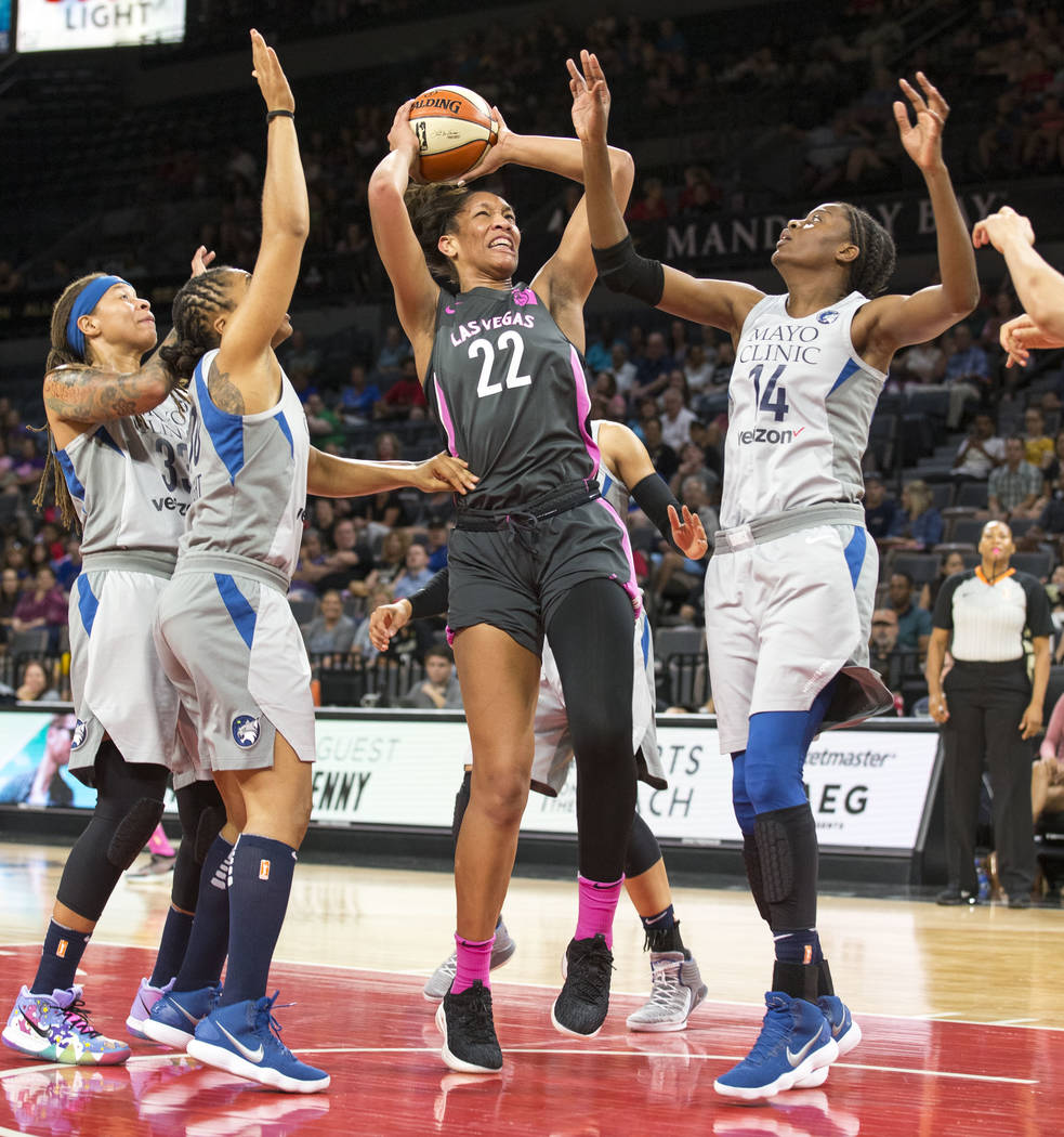 Las Vegas Aces center A'ja Wilson (22) goes up for a shot against Minnesota Lynx defenders during the first half of a WNBA basketball game at the Mandalay Bay Events Center in Las Vegas on Thursda ...