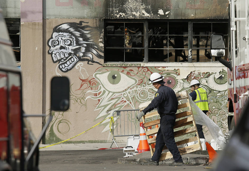 A member of the Alameda County Sheriff's Department, left, carries away a pallet outside the site of a warehouse fire in Oakland, Calif.on Wednesday, Dec. 7, 2016. (AP Photo/Eric Risberg, File)