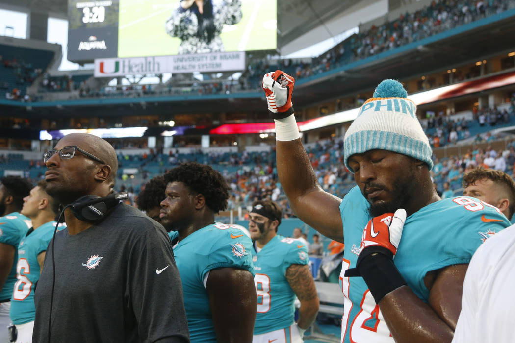 Miami Dolphins defensive end Robert Quinn (94) raises his right fist during the singing of the national anthem, before the team's NFL preseason football game against the Tampa Bay Buccaneers, Thur ...