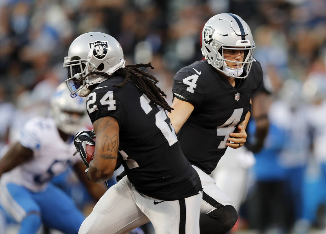 Oakland Raiders quarterback Derek Carr (4) hands off to running back Marshawn Lynch (24) during the first half of an NFL preseason football game against the Detroit Lions in Oakland, Calif., Frida ...