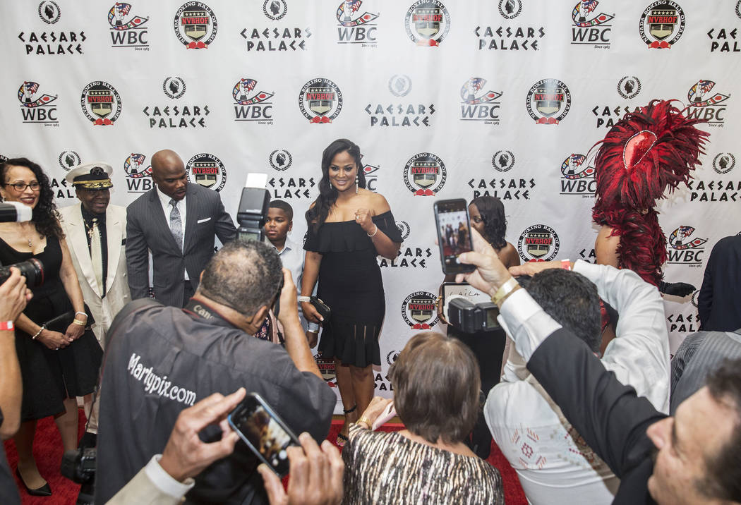 Laila Ali, middle, daughter of boxing great Muhammad Ali, takes photos on the red carpet before the start of the Nevada Boxing Hall of Fame gala on Saturday, Aug. 18, 2018, at Caesars Palace, in L ...