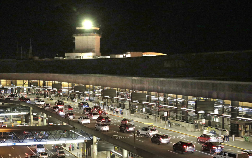 Traffic arrives at Sea-Tac International Airport terminal Friday evening, Aug. 10, 2018, in SeaTac, Wash. (AP Photo/Elaine Thompson)