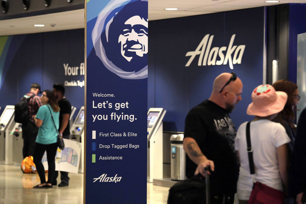 People stand in the Alaska Airlines ticket area at Sea-Tac International Airport Friday, Aug. 10, 2018, in SeaTac, Wash. (AP Photo/Elaine Thompson)