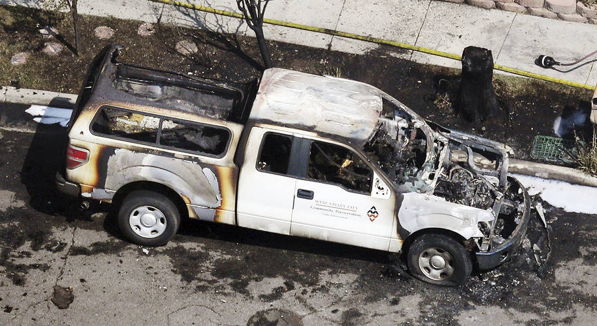 A burned West Valley City Community Preservation Code Enforcement vehicle is seen near the place where a structure fire and fatal shooting occurred in West Valley City, Utah, on Thursday, Aug. 9, ...