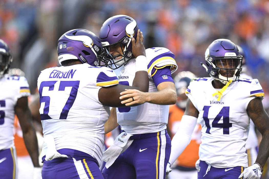 Minnesota Vikings quarterback Kirk Cousins, right, celebrates with center Cornelius Edison (67) after connecting with wide receiver Stefon Diggs in the first quarter of an NFL football game agains ...
