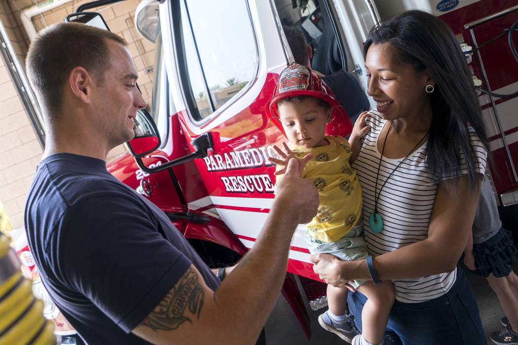 Phenix Teixeira, 2, and his mother Jade Teixeira meet firefighter Eric Whaley at Fire Station 92 in Henderson, Saturday, Aug. 11, 2018. City of Henderson Fire Department holds an open house at a d ...
