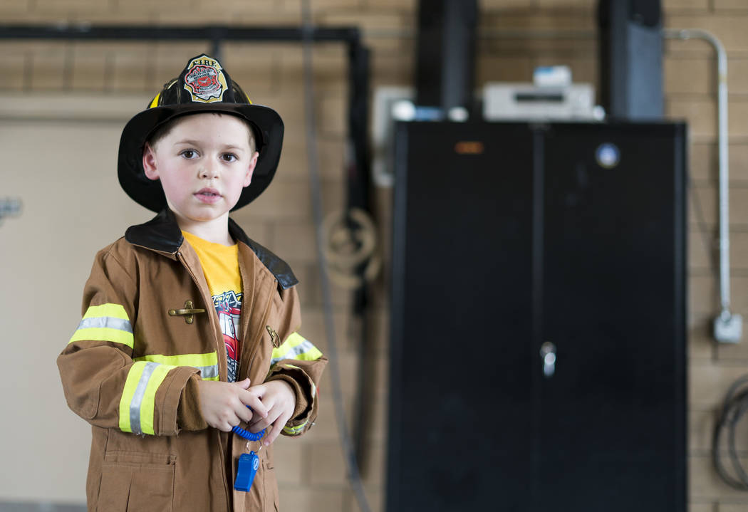 Everett Bambauer, 4, tries on a kid-sized firefighter uniform at Fire Station 92 in Henderson, Saturday, Aug. 11, 2018. City of Henderson Fire Department holds an open house at a different fire st ...