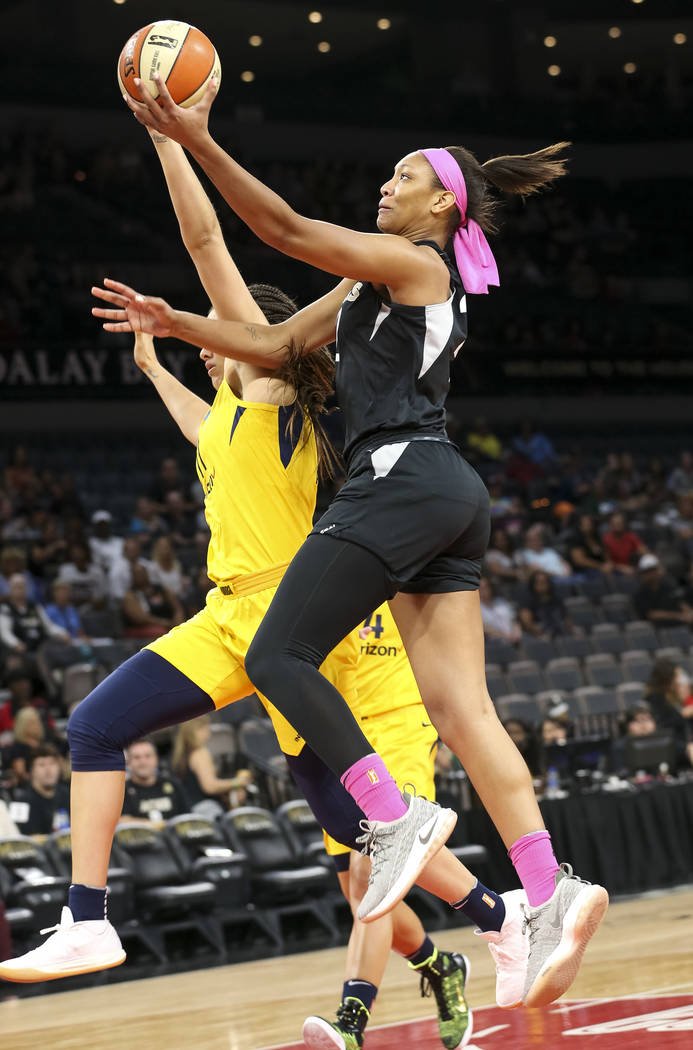 Las Vegas Aces center A'ja Wilson (22) drives to the hoop past Indiana Fever forward Natalie Achonwa (11) during the first half of a WNBA basketball game at the Mandalay Bay Events Center on Satur ...