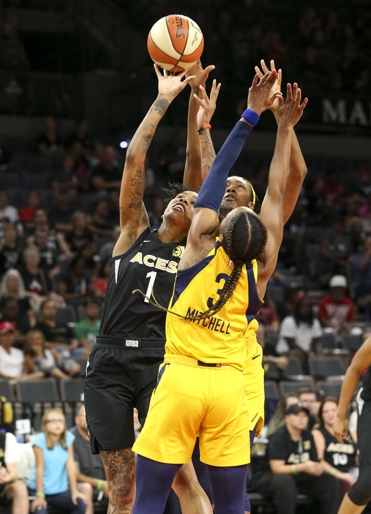 Las Vegas Aces forward Tamera Young (1), Indiana Fever guard Tiffany Mitchell (3) and Fever center Kayla Alexander (40) vie for the ball during the first half of a WNBA basketball game at the Mand ...