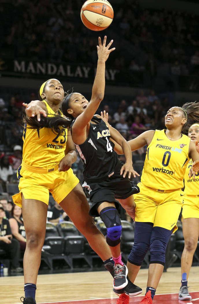 Las Vegas Aces guard Moriah Jefferson (4) takes a shot against Indiana Fever forward Stephanie Mavunga (23) and Fever guard Kelsey Mitchell (0) during the first half of a WNBA basketball game at t ...