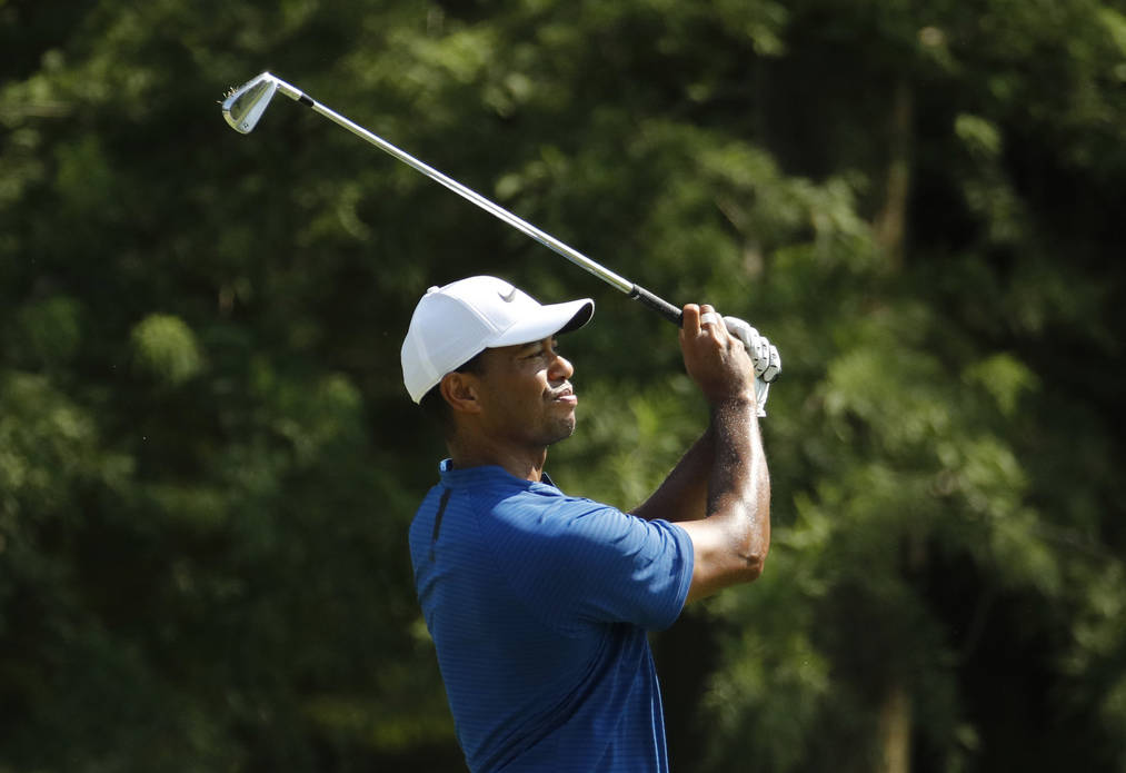 Tiger Woods watches his tee shot on the 13th hole during the third round of the PGA Championship golf tournament at Bellerive Country Club, Saturday, Aug. 11, 2018, in St. Louis. (AP Photo/Charlie ...