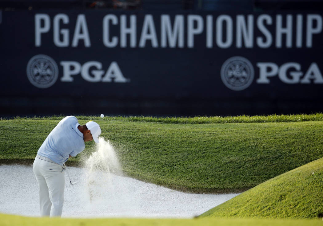Brooks Koepka hits out of a bunker on the 18th hole during the third round of the PGA Championship golf tournament at Bellerive Country Club, Saturday, Aug. 11, 2018, in St. Louis. (AP Photo/Charl ...