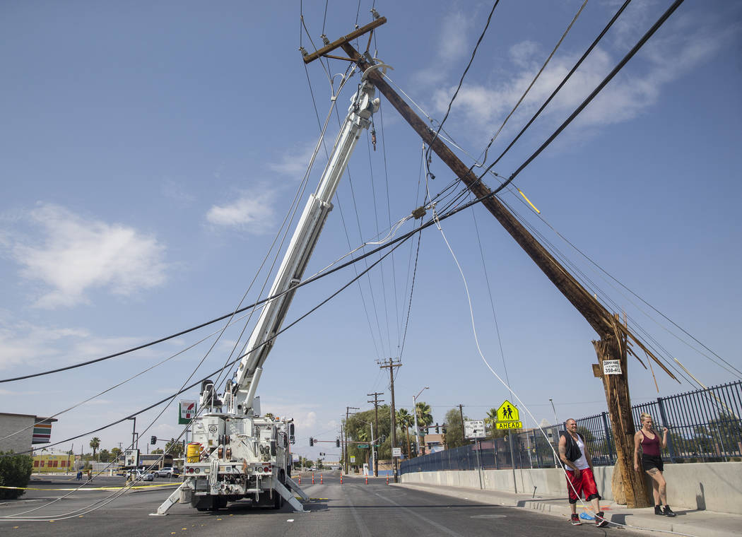 Las Vegas residents pass by NV Energy crews working to restore power in the area of Fremont Street and Bruce Street on Sunday, Aug., 12, 2018, in Las Vegas. More than 60,000 people lost power Satu ...
