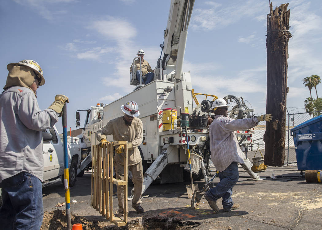 NV Energy crews work to restore power in the area of Fremont Street and Bruce Street on Sunday, Aug., 12, 2018, in Las Vegas. More than 60,000 people lost power Saturday night due to a severe thun ...