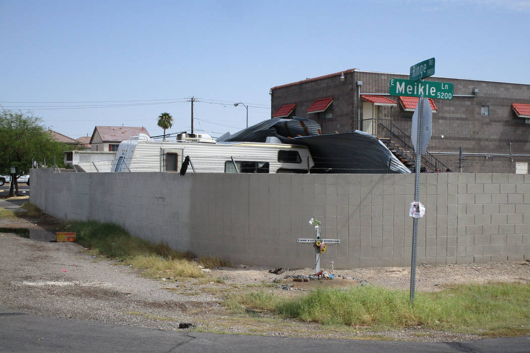 Workers try to dismantle a sheet metal awning that collapsed in Saturday night's storm behind a business in east Las Vegas near Lake Mead Boulevard and Nellis Boulevard on Sunday, August 12, 201 ...