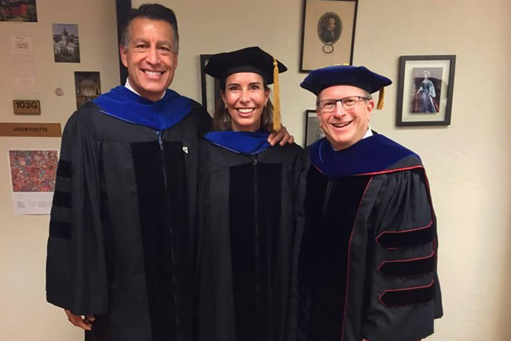 From left to right, Governor Brian Sandoval, Lauralyn McCarthy and Dean Al Stavitsky pose before the 2018 Spring Reynolds School Commencement. (UNR)