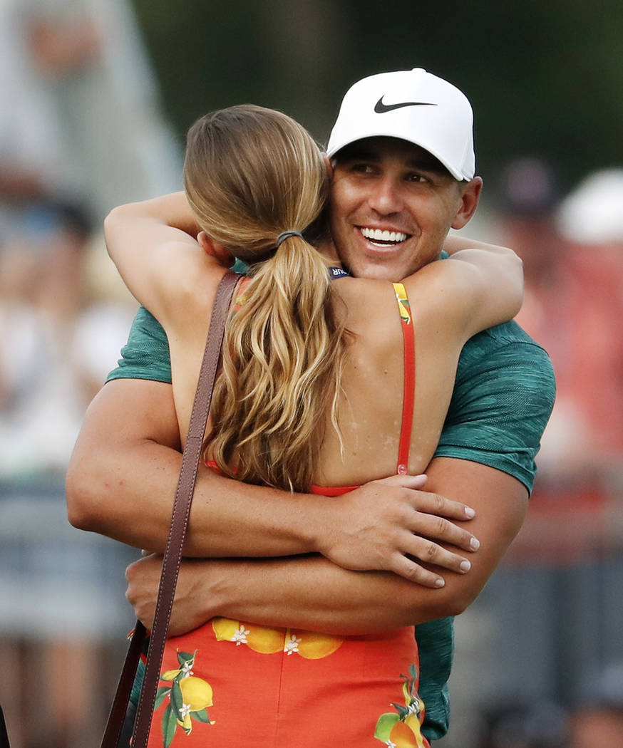 Brooks Koepka hugs his girlfriend, Jena Sims, after Koepka won the PGA Championship golf tournament at Bellerive Country Club, Sunday, Aug. 12, 2018, in St. Louis. (AP Photo/Jeff Roberson)