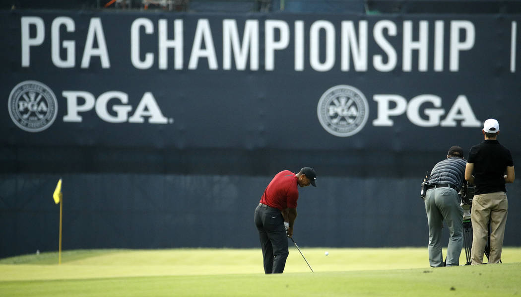 Tiger Woods hits onto the 18th green during the final round of the PGA Championship golf tournament at Bellerive Country Club, Sunday, Aug. 12, 2018, in St. Louis. (AP Photo/Charlie Riedel)