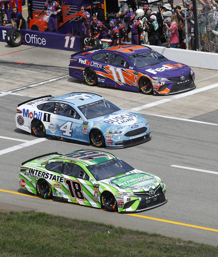 Kyle Busch (18), Kevin Harvick (4) and Denny Hamlin (11) race off pit lane during a NASCAR Cup Series auto race at Michigan International Speedway in Brooklyn, Mich., Sunday, Aug. 12, 2018. (AP Ph ...