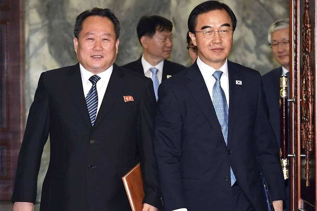 South Korean Unification Minister Cho Myoung-gyon, right, and his North Korean counterpart Ri Son Gwon arrive to hold their meeting at the northern side of Panmunjom in the Demilitarized Zone, Nor ...