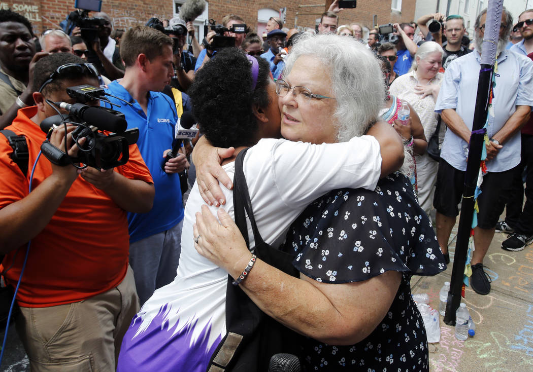 Susan Bro, mother of Heather Heyer who was killed during last year's Unite the Right rally, embraces supporters after laying flowers at the spot her daughter was killed in Charlottesville, Va., Su ...
