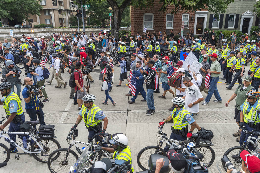 """White nationalists, led by Jason Kessler, center, wearing a suit and carrying a flag, march to Lafayette Square during the """"Unite the Right 2"""" rally in Washington, Sunday, Aug. 12, 2018. ..."""