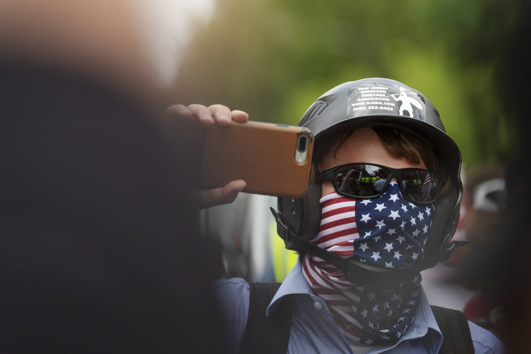 """A white nationalist holds his phone while marching to Lafayette Square during the """"Unite the Right 2"""" rally in Washington, Sunday, Aug. 12, 2018. (Craig Hudson/Charleston Gazette-Mail vi ..."""