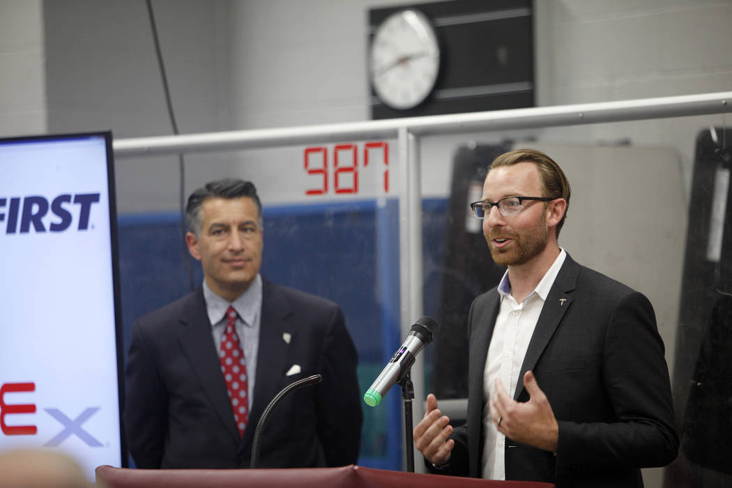 Chris Reilly, workforce development and education coordinator for Tesla, speaks next to Gov. Brian Sandoval at an event where Tesla and education leaders revealed new opportunities for robotics fo ...