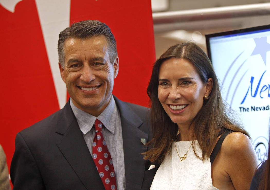 Newlyweds Gov. Brian Sandoval and Las Vegas gaming executive Lauralyn McCarthy pose for photos at an event where Tesla and education leaders revealed new opportunities for robotics for education t ...