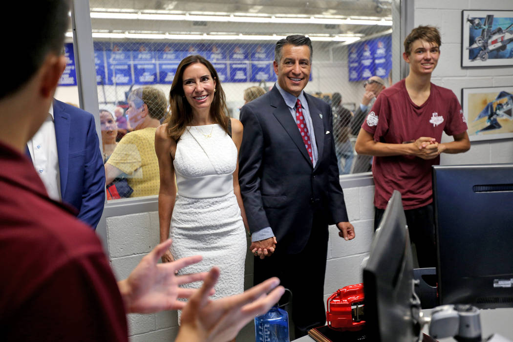 Gov. Brian Sandoval and his wife Lauralyn McCarthy speak to Riki Osako, 16, left, at an event where Tesla and education leaders revealed new opportunities for robotics for education throughout the ...