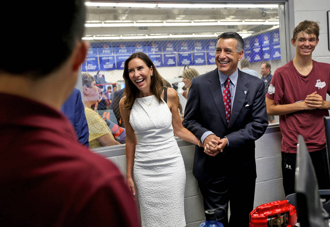 Gov. Brian Sandoval and his wife Lauralyn McCarthy laugh with Riki Osako, 16, left, at an event where Tesla and education leaders revealed new opportunities for robotics for education throughout t ...