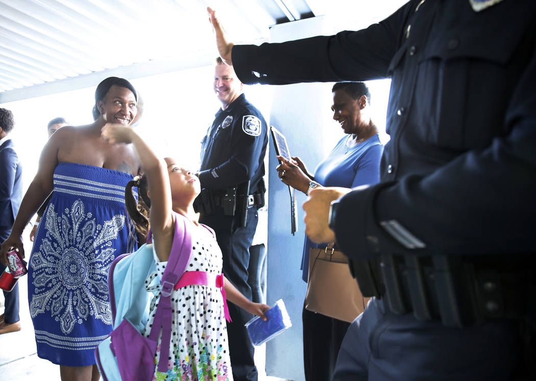 Matt Kelly Elementary School student Tiaryana Foster, 5, welcomed by community and business leaders, including North Las Vegas police officer Aaron Patty, right, with an inspirational welcome and ...