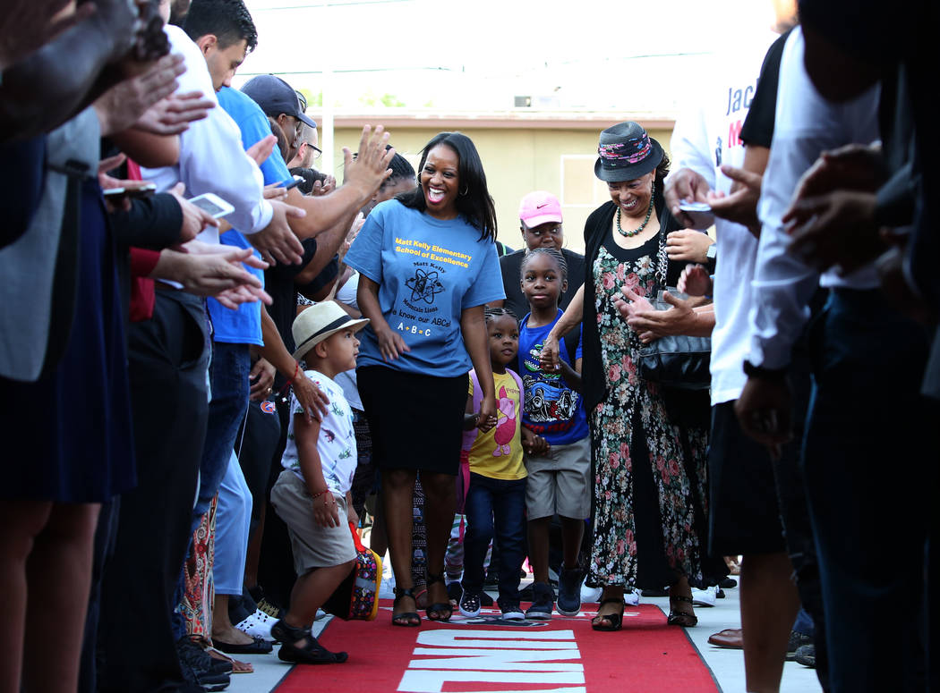 Matt Kelly Elementary School Principal, Alaina Criner, left, walks the red carpet with students as community and business leaders welcome students as they arrive on their first day of school on Mo ...