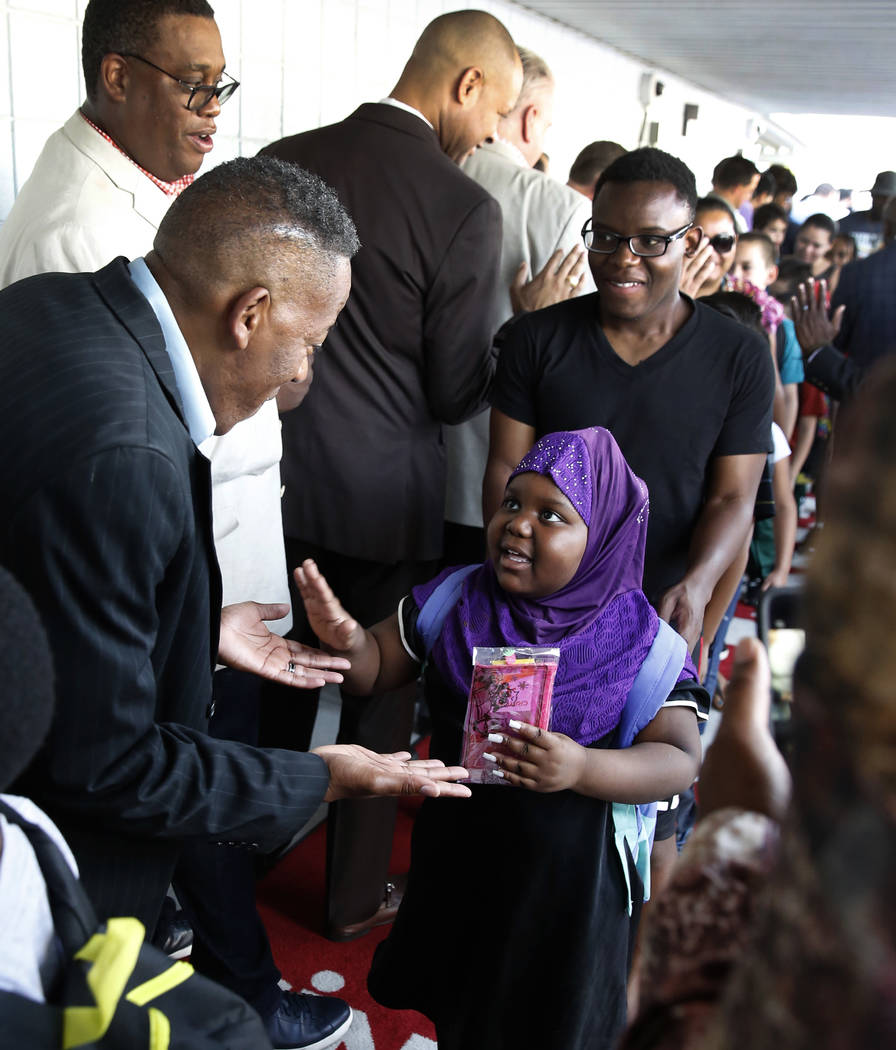Community and business leaders, including Clark County Commissioner Lawrence Weekly, left, welcome Matt Kelly Elementary School student Amania Mohamed, 6, as she arrives on her first day of school ...