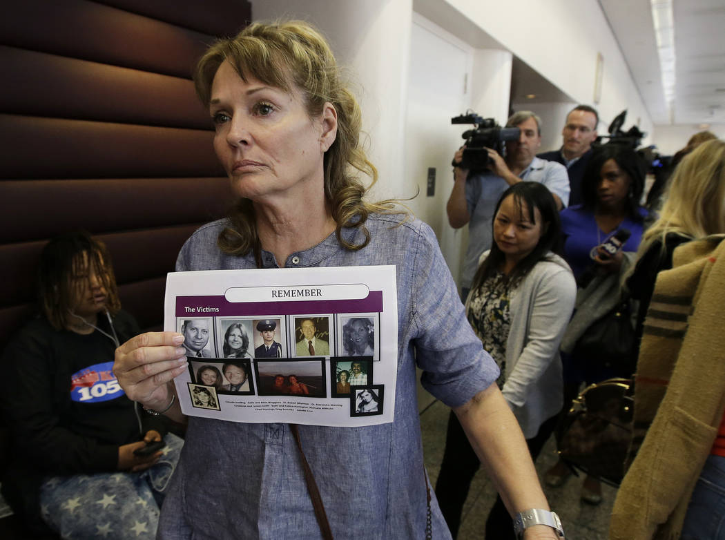 Melanie Barbeau displays photos of murder victims believed to be slain by the Golden State Killer as she leaves a hearing for suspect Joseph DeAngelo in Sacramento, Calif., on May 14. Prosecutors ...