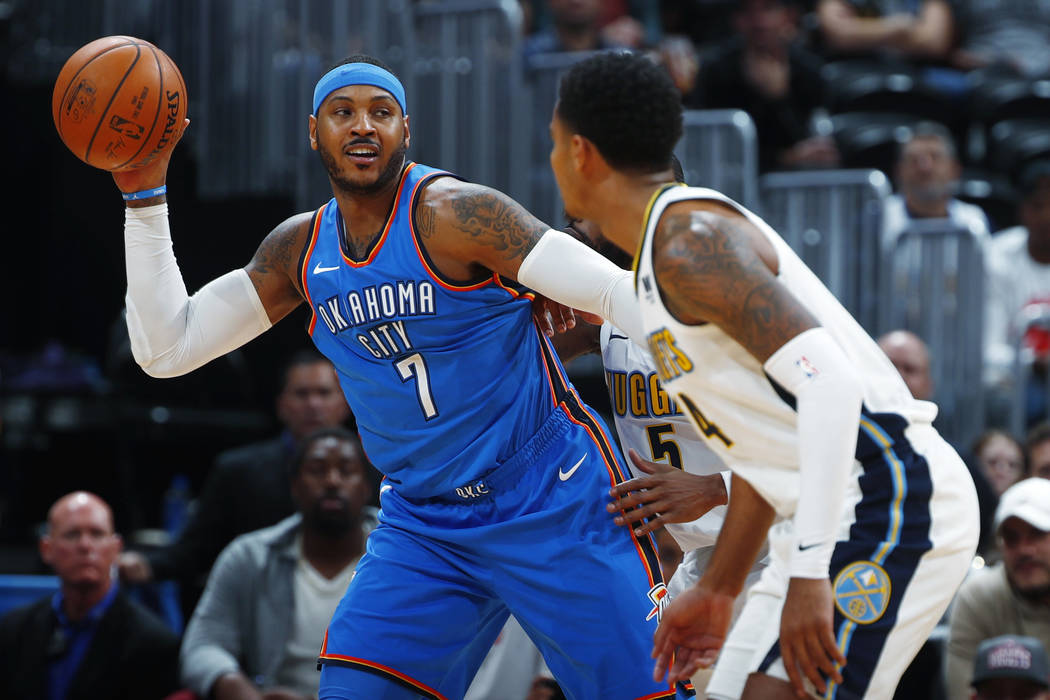 This Nov. 9, 2017, file photo shows Oklahoma City Thunder forward Carmelo Anthony, left, looking to pass the ball as Denver Nuggets guards Gary Harris, front right, and Will Barton defend during t ...