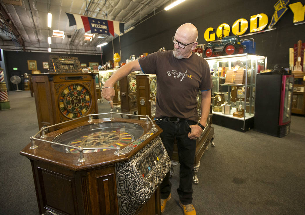 Don Grimmer, vice president of Morphy Auctions, demonstrates the Cailli Bros. 5 cent, 7-way roulette wheel slot machine on display at the company's warehouse located at 4520 Arville Street in Las ...