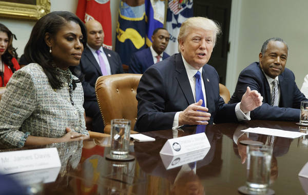 FILE - In this Feb. 1, 2017, file photo, President Donald Trump, center, is flanked by White House staffer Omarosa Manigault Newman, left, and then-Housing and Urban Development Secretary-designa ...