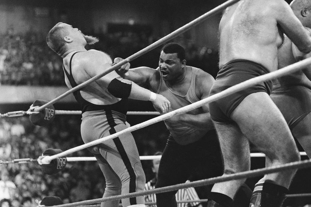 """This April 7, 1986, file photo shows Chicago Bears' William Perry, right, landing a punch on pro wrestler Jim """"The Anvil"""" Neidhart during the """"Over-The-Top-Rope"""" battle royal at Wrestlemania 2 in ..."""