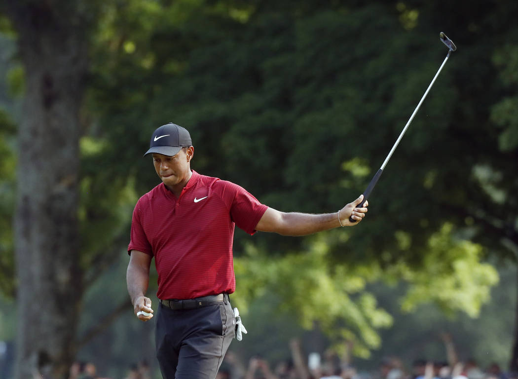 Tiger Woods walks off the 18th green after sinking a birdie putt during the final round of the PGA Championship golf tournament at Bellerive Country Club, Sunday, Aug. 12, 2018, in St. Louis. (AP ...