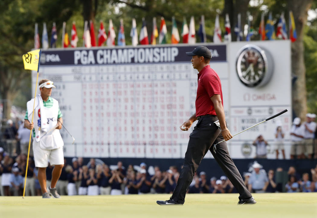 Tiger Woods walks off the 18th green after making a birdie during the final round of the PGA Championship golf tournament at Bellerive Country Club, Sunday, Aug. 12, 2018, in St. Louis. (AP Photo/ ...